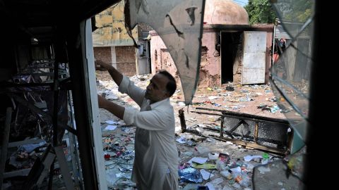 A worker inspects his damaged shop following violent protests in Peshawar, Pakistan, on Saturday.
