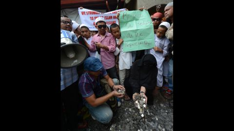 """Philippine Muslims gather coins they collected from the provinces to be used to pay for filing a petition before the Philippine Supreme Court in Manila on Monday asking for local authorities to ban the controversial """"Innocence of Muslims"""" film from being posted on the Internet.  Hundreds of Muslim protesters in the Philippines called for a ban on the film before the U.S. Embassy."""