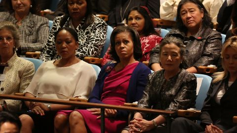 U.S. first lady Michelle Obama, center, listens to her husband speak on Tuesday.