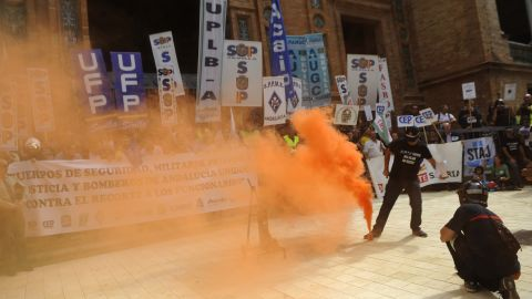 Protesters walk through smoke thrown by firemen and policemen during a demonstration of public service workers in Spanish Sevilla on September 29, 2012.