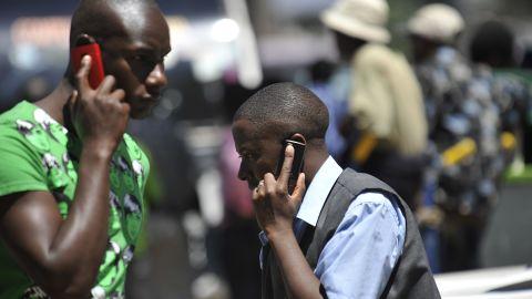People walk while speaking on the phone in Nairobi, Kenya on October 1, 2012.