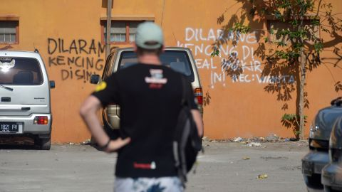 """Words spray-painted on the side of a wall near the Sari Club bomb site read in Indonesian """"don't urinate here."""" Campaigners are fighting for a permanent memorial to be build on the site, a peace park to allow for quiet reflection, but negotiations have been delayed over price."""