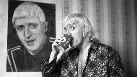 """The first presenter of long-running music program """"Top of the Pops,"""" Savile poses by a portrait of himself in February 1965, while enjoying his regular breakfast of Coke and a cigar in a central London hotel room."""