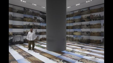 """Ai Weiwei poses in 2009 at the Mori Art Museum inTokyo with his work """"Provisional Landscape"""" (2002-2008). It's now on display at the Hirshhorn Museum in Washington."""