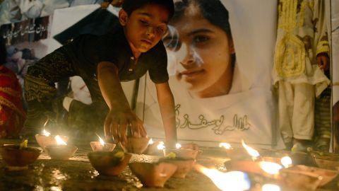 A Pakistani youth places an oil lamp next to a photograph of teen activist Malala Yousufzai on Friday, October 12, 2012, in Karachi, Pakistan.