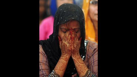 A Pakistani female covers her face during prayers in Karachi.