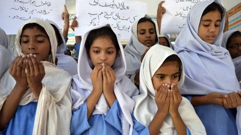 """Pakistani school girls pray for the Malala's recovery. Over the weekend, the teen moved her limbs after doctors """"reduced sedation to make a clinical assessment,"""" military spokesman Maj. Gen. Asim Bajwa said."""