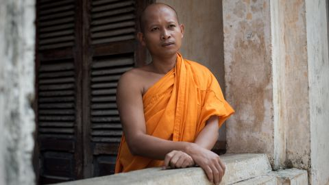 A Cambodian Buddhist monk stands on a balcony as people pay respects in front of the Royal Palace in Phnom Penh on Tuesday, October 16.
