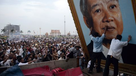 Cambodian people watch as workers install a portrait of Sihanouk in front of the Royal Palace on Tuesday.