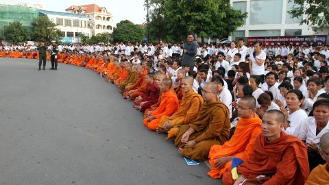Cambodian Buddhist monks sit with mourners waiting for a convoy transporting the late former king's coffin at the Independence Monument in Phnom Penh which commemorates the end of French rule over Cambodia in 1954.