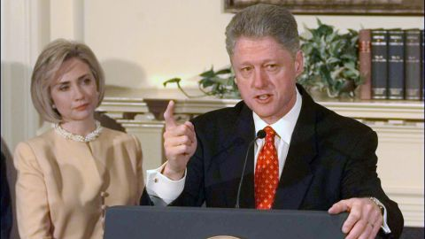 """Clinton looks on as her husband discusses the Monica Lewinsky scandal in the Roosevelt Room of the White House on January 26, 1998. Clinton declared, """"I did not have sexual relations with that woman."""" In August of that year, Clinton testified before a grand jury and admitted to having """"inappropriate intimate contact"""" with Lewinsky, but he said it did not constitute sexual relations because they had not had intercourse. He was impeached in December on charges of perjury and obstruction of justice."""