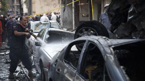 A Lebanese firefighter douses cars at the site of an explosion in Beirut's Christian neighbourhood of Ashrafieh.