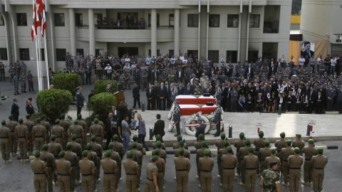 Officers and mourners gather around al-Hassan's coffin during his funeral on Sunday.