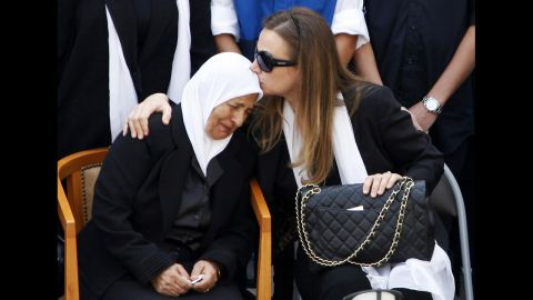 The mother and wife of the slain intelligence officer mourn Sunday.