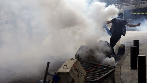 A demonstrator runs for cover from tear gas fired by Lebanese police on Sunday.