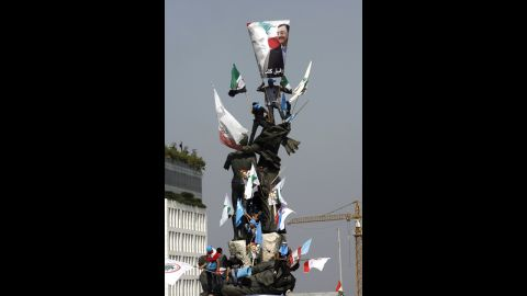 Protesters climb a statue Sunday during the funeral of al-Hassan.