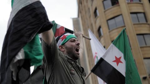 An anti-government protester waves a pre-Baath Syrian flag at a demonstration outside the govermental palace in Beirut, Lebanon, after a funeral for al-Hassan and his bodyguard on Sunday. The two men and one other person were killed in a car bombing on Friday.