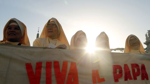 Nuns hold a banner at the ceremony on Sunday.