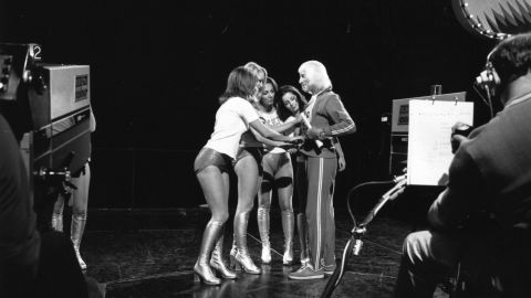 """Dancers on the BBC TV show """"Top of the Pops"""" adjust Savile's track suit top for him during the making of the show in 1973."""