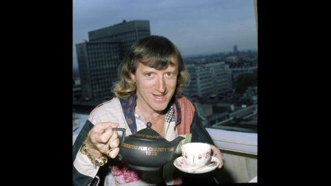 Savile pours a cup of tea.
