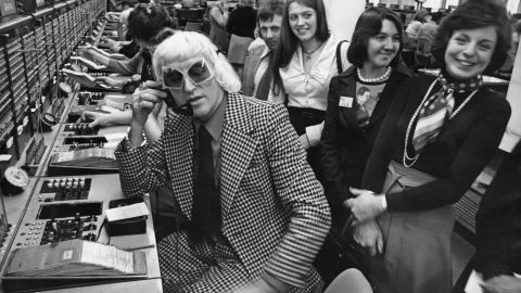 """Savile calls from the Wren House International Telephone Exchange in London in 1975 as part of a """"Fun And Happiness Weekend,"""" organized by the National Association of Youth Clubs."""