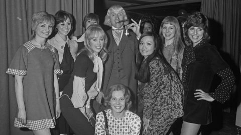 """Savile shows off his Order of the British Empire to members of the """"Second Generation"""" song and dance troupe."""