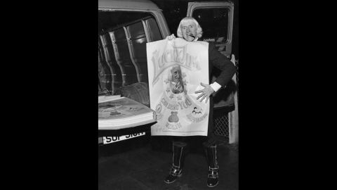 """Savile holds a newly-printed """"Lucky Jim"""" poster. The posters feature a portrait of the DJ, along with a text reading: """"The Lucky Jim poster can bring you health, wealth, happiness. This is a genuine duplicate signature and what's more Jimmy has actually touched YOUR poster!"""""""