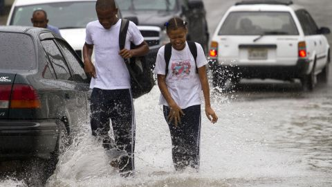 Dominican school children walk in the flooded streets of Santo Domingo before the arrival of Hurricane Sandy on Thursday, October 24, 2012.