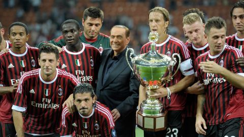 Berlusconi, then owner of the Italian soccer club AC Milan, celebrates with the players after the team won the Luigi Berlusconi Trophy in August 2011. The trophy is in honor of Berlusconi's father.