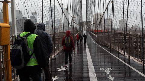 People walk across a rainy Brooklyn Bridge as New York City braces for Hurricane Sandy's arrival.