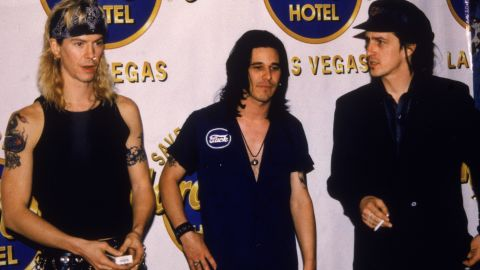 Duff McKagan, left to right, Gilby Clarke, and Izzy Stradlin of Guns N' Roses pose in front of a Hard Rock Cafe banner in Las Vegas, Nevada, in 1992.