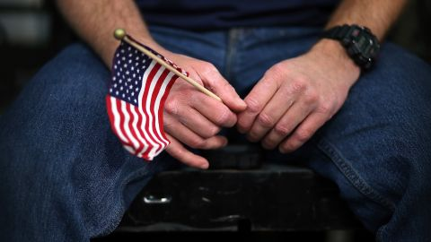 A Mitt Romney supporter holds an American flag during a campaign event at Meadow Event Park.