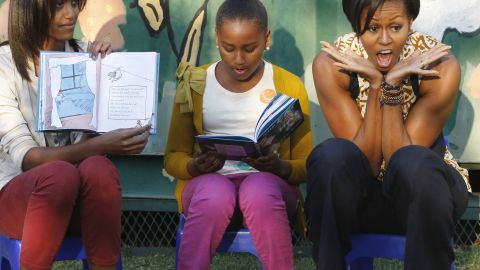 """First lady Michelle Obama, daughters Malia, left, and Sasha, center, take turns reading to children from """"The Cat in the Hat"""" by Dr. Seuss as they visit South Africa in 2011."""