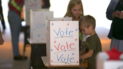 Gaberyel Chandler casts his vote with the help of safety patrol officer Cheyenne Roberts during a mock presidential election Tuesday at Emerald Shores Elementary School in Ocala, Florida.