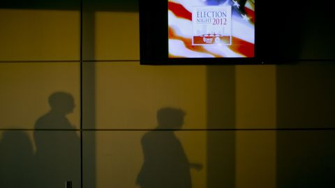 """Shadows were cast on a wall next to a television advertising """"Election Night 2012"""" inside the Boston Convention & Exhibition Center, where Republican presidential candidate Mitt Romney was scheduled to speak Tuesday evening."""