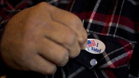 """A man puts on an """"I Voted"""" sticker after casting his ballot in Otter Creek, Iowa, on Tuesday."""