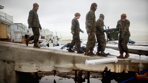 """U.S. Marines from the 8th Engineer Support Battallon out of Camp Lejeune, North Carolina, move a generator to pump out floodwater from a street after a nor'easter on Thursday, November 8, in the Breezy Point neighborhood of Queens, New York. The nor'easter, which dumped 2 feet of snow in some places, complicates Superstorm Sandy recovery efforts. That storm killed at least 111 people in the region and knocked out power to millions of customers.  <a href=""""http://www.cnn.com/2012/10/30/us/gallery/sandy-damage/index.html"""" target=""""_blank"""">See photos of the aftermath of Sandy</a>."""