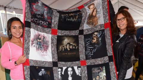 """Two fans hold up a """"Twilight"""" quilt."""