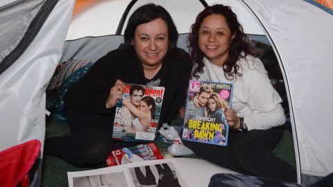 "Fans hold up magazines featuring ""Twilight"" actors Robert Pattinson and Kristen Stewart."