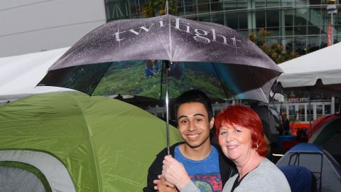 """Two fans brave the rain with a """"Twilight"""" umbrella at tent city."""