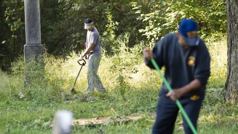 """Volunteers clear the overgrown brush from Linwood Cemetery, which tells the story of Macon's African-American community. Sgt. Rodney Davis' mother insisted on burying him there, instead of Arlington National Cemetery.  Davis' sister, Debra Ray said: """"Mother would say if Rodney wasn't there nobody would care about the cemetery."""""""