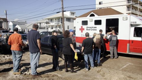 Residents who returned to their damaged homes line up for a hot meal served from a Red Cross vehicle on Samson Avenue in Seaside Heights, New Jersey, on Monday.
