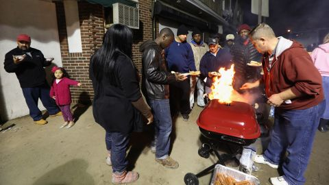 People gather for donated food beneath a spotlight in an area still without power on Monday in Rockaway.