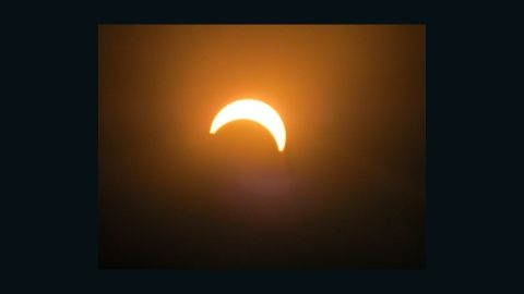 """""""I thought it would be cool to take a few photos because I haven't seen an eclipse in my lifetime, says iReporter <a href=""""http://ireport.cnn.com/people/sjhill87"""">Samuel Hill</a> who shot this picture in Wellington, New Zealand. """"Most people were really excited once they got to look through the solar lenses to see the eclipse."""""""