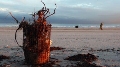 A woman walks past debris on Rockaway Beach on Tuesday.