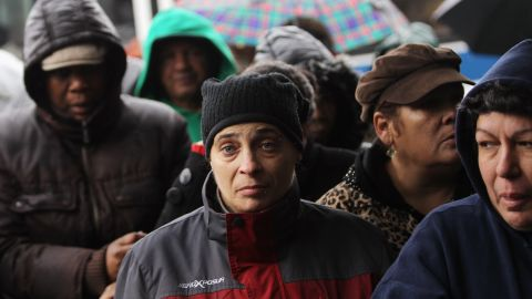 People wait in line to collect some of the 1,500 donated coats from New York Cares on Tuesday in Queens.  The charity started its annual coat drive early this year to assist those affected by Superstorm Sandy. It hopes to collect 200,000 coats this winter.