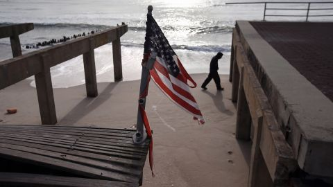 A tattered U.S. flag flies over the storm-damaged boardwalk in the Rockaway section of Queens on Thursday.