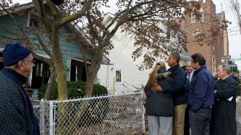 President Barack Obama embraces a local resident on Cedar Grove Avenue during a visit to Staten Island on Thursday, November 15.
