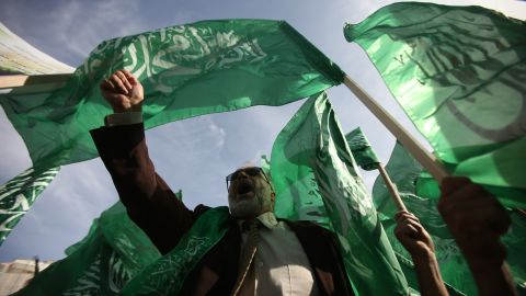 Palestinian protesters hold up the Hamas flag during a rally Friday, November 16, in the West Bank city of Ramallah.