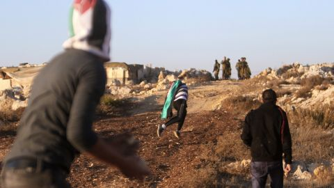Palestinian youths throw stones at Israeli security forces Friday, November 16, in a West Bank village near Bethlehem.